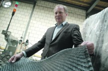 Directeur Coert Meihuizen van weverij A.C. ter Kuile toont het weefsel gemaakt van 6 mm breed kunststofcomposiettape: 'We gaan inzetten op nieuwe materialen. Weaving Future Materials.' (Foto: Saxion TPAC)